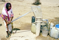 A young woman pumps water in Eritrea © UN Photo/Milton Grant
